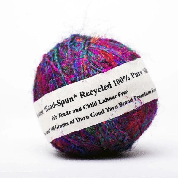 A multicolor ball of yarn with a tag around it